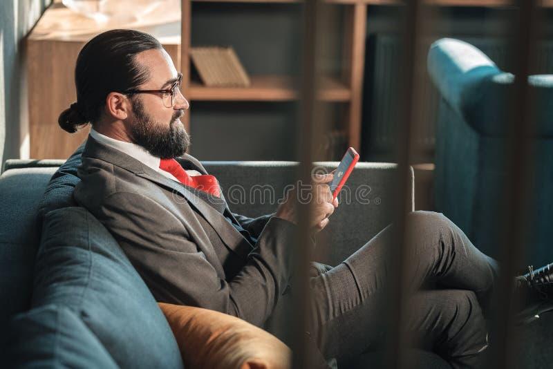 Zakenman die glazen dragen die zijn bericht van de smartphonelezing houden royalty-vrije stock fotografie