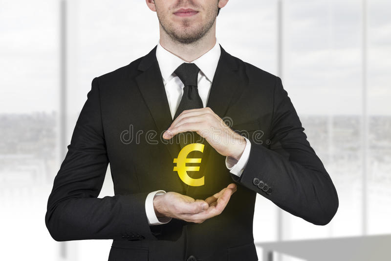 Zakenman die gouden euro symbool beschermen stock foto