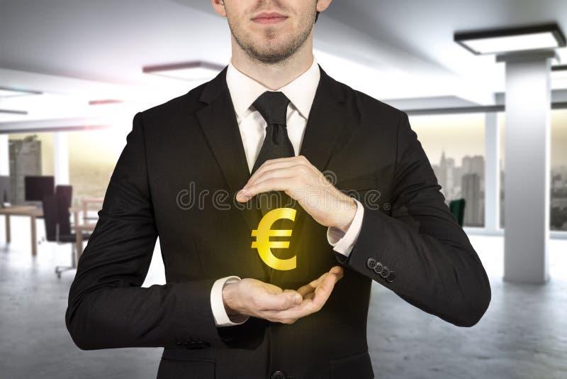 Zakenman die gouden eurosymbol beschermen stock afbeelding