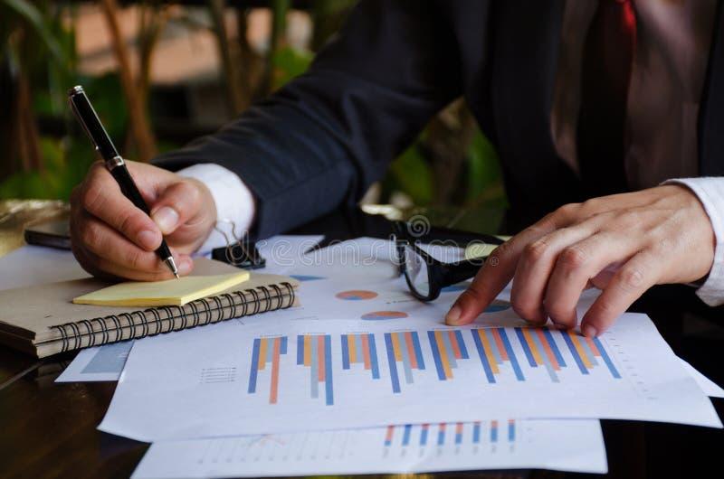 Zakenman die grafieken en grafieken op bureau analyseren stock foto's