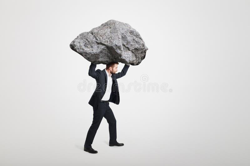 Zakenman die grote steen dragen royalty-vrije stock afbeeldingen