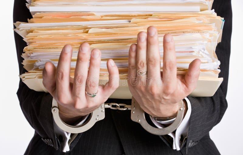 Zakenman die in handcuffs dossieromslagen houdt stock fotografie