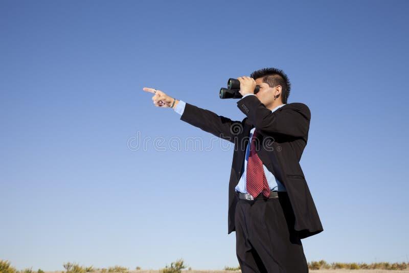 Zakenman die hoewel verrekijkers kijkt stock foto