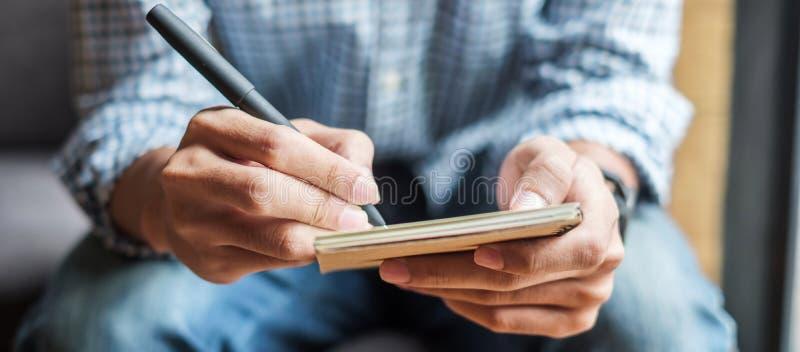 Zakenman die iets op notitieboekje in bureau, hand schrijven van de pen van de mensenholding met handtekening op document rapport stock foto