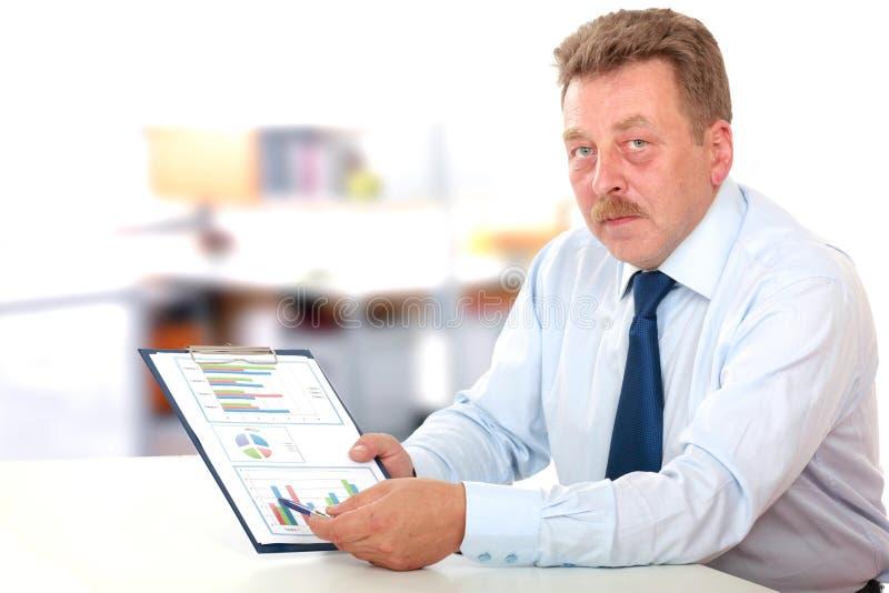 Zakenman die investeringsgrafieken analyseren bij van hem stock afbeeldingen