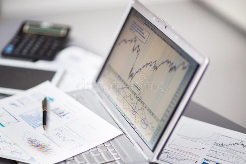 Zakenman die investeringsgrafieken met laptop analyseren royalty-vrije stock afbeelding