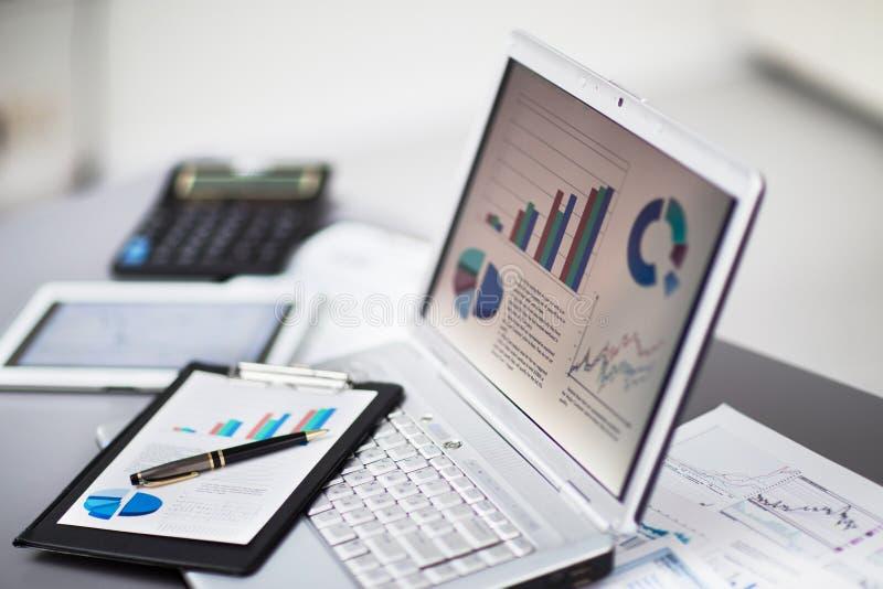 Zakenman die investeringsgrafieken met laptop analyseren stock afbeeldingen