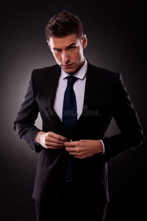 Zakenman die jasje dichtknoopt, dat gekleed wordt stock afbeelding