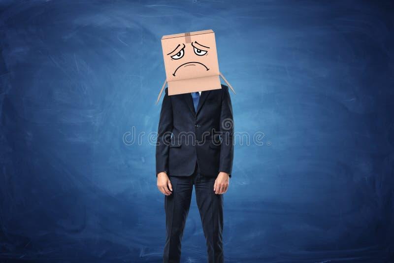 Zakenman die kartondoos met getrokken droevig gezicht op zijn hoofd dragen stock afbeeldingen
