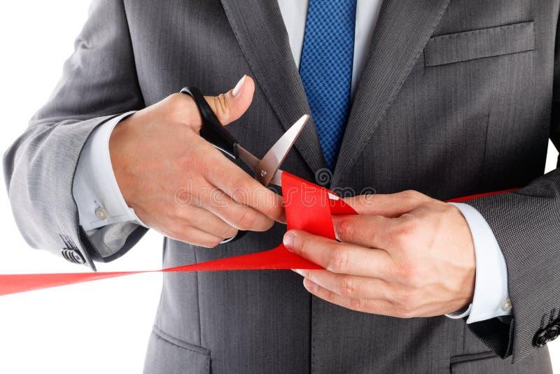Zakenman die in kostuum rood lint met paar van schaar ISO snijden royalty-vrije stock foto's