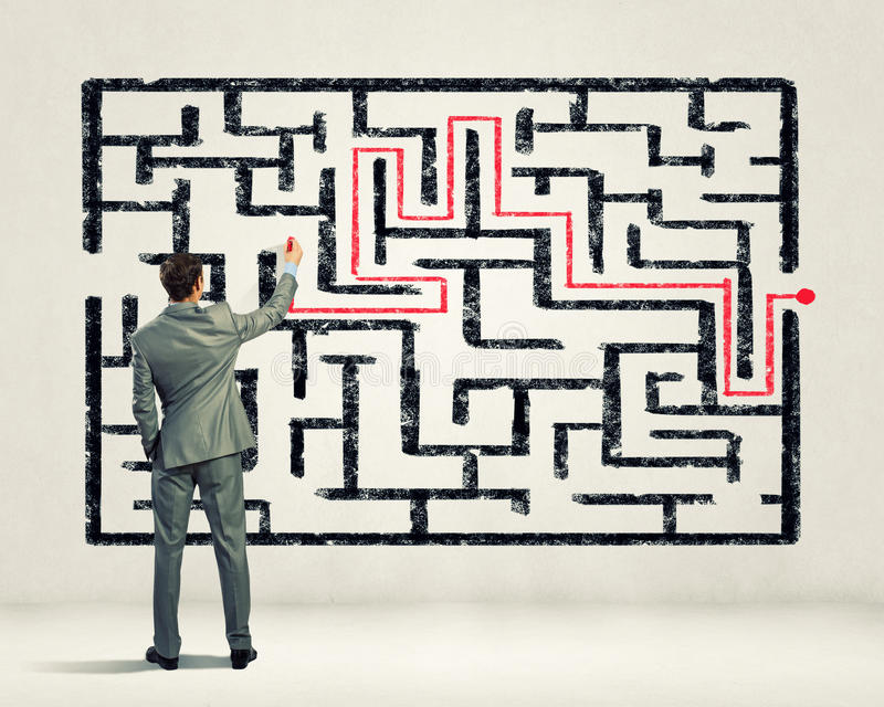 Zakenman die labyrintprobleem oplossen stock afbeelding