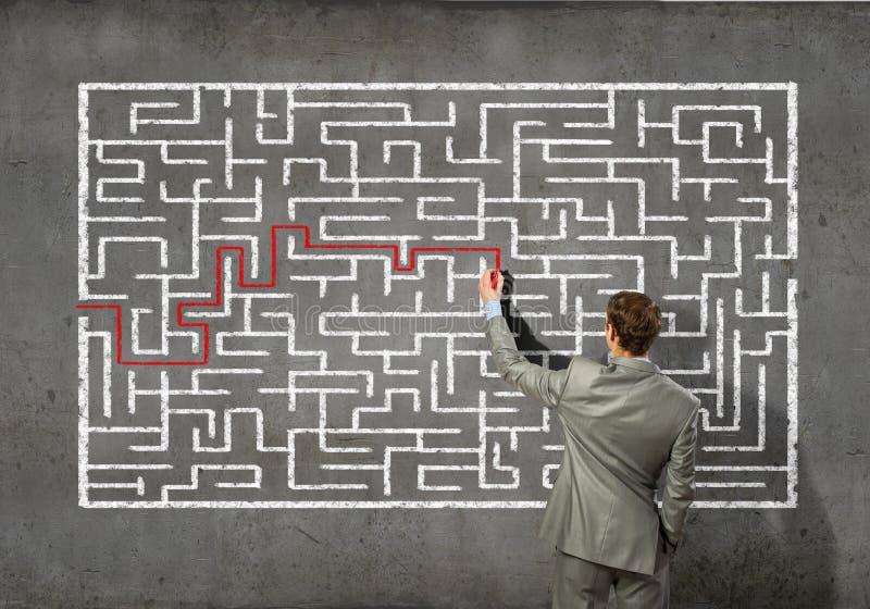 Zakenman die labyrintprobleem oplossen stock afbeeldingen