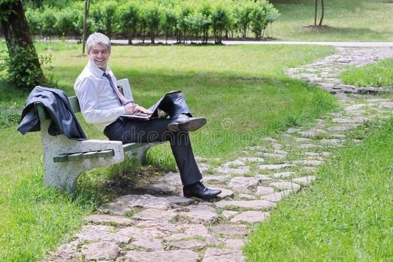 Zakenman die laptop in een park met behulp van stock foto's