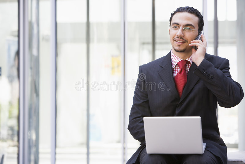 Zakenman die laptop en mobiele telefoon buiten met behulp van royalty-vrije stock foto
