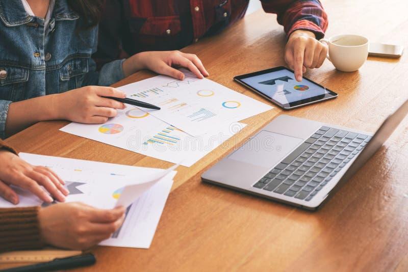 Zakenman die laptop en tabletpc met behulp van terwijl het samenwerken van en het bespreken van zaken in een vergadering stock afbeeldingen