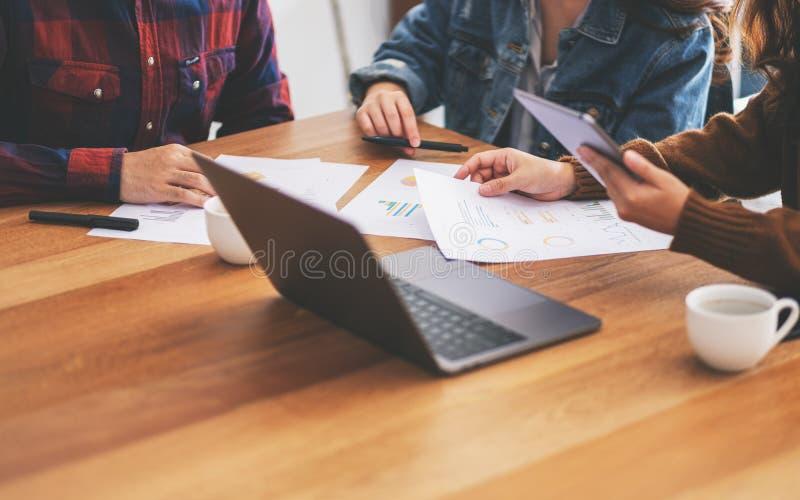 Zakenman die laptop en tabletpc met behulp van terwijl het samenwerken van en het bespreken van zaken in een vergadering royalty-vrije stock foto