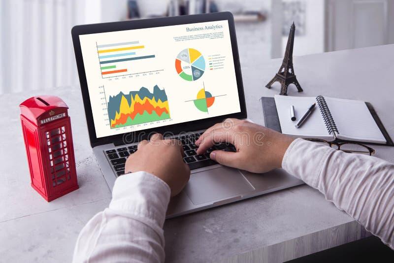 Zakenman die laptop met behulp van die statistiekengegevens over laptop het scherm analyseren, die met grafiekengrafieken online  stock foto's