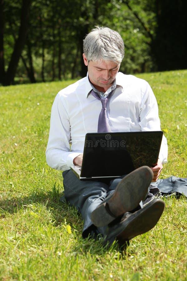 Zakenman die laptop op een weide met behulp van stock foto