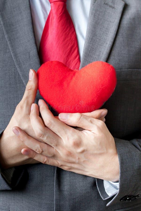 Zakenman die medeleven tonen die rood hart op zijn borst houden stock fotografie
