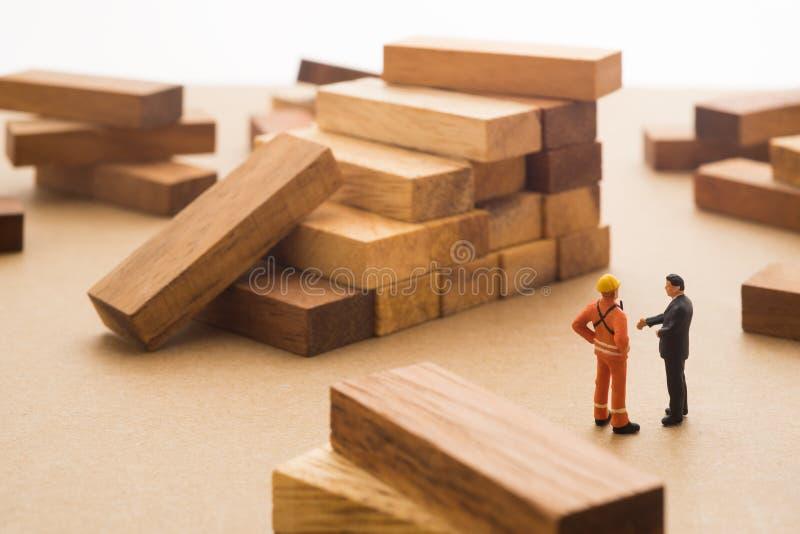 Zakenman die met bouwwerfmanager over houten st spreken stock foto's