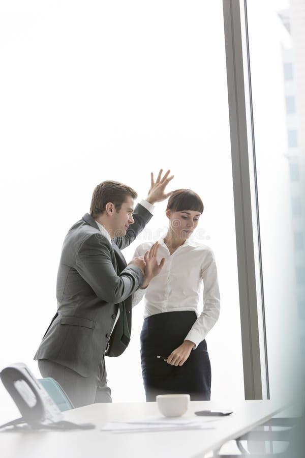 Zakenman die met boze onderneemster spreken die zich tegen venster op modern kantoor bevinden stock foto's