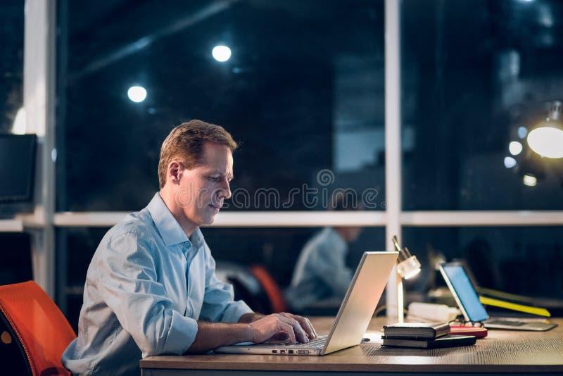 Zakenman die met computer laat bij nacht werken royalty-vrije stock fotografie