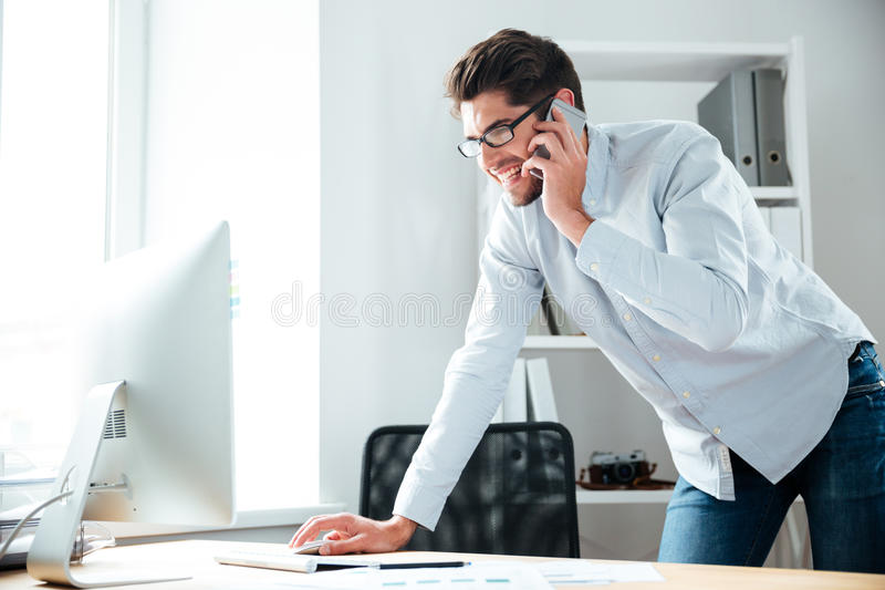 Zakenman die met computer werken en op celtelefoon spreken stock foto's