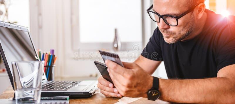 Zakenman die met creditcard op slimme telefoon betalen stock foto