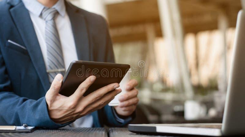 Zakenman die met digitale tablet en laptop met financiële bedrijfsstrategie bij een koffie van de koffiewinkel werken stock fotografie