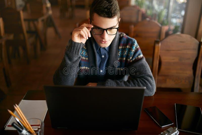 Zakenman die met documenten aan laptop tablet werken en slimme telefoon op lijst Freelancer het doorbladeren Web in koffie knap stock fotografie