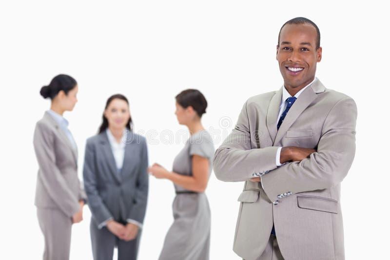 Zakenman die met drie medewerkers glimlachen die in backgro spreken stock afbeeldingen
