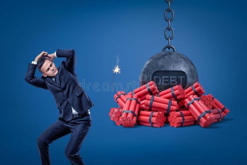 Zakenman die met handen en geketende bal met een 'SCHULD 'teken beschermen over rode dynamietstokken met aangestoken zekering royalty-vrije illustratie
