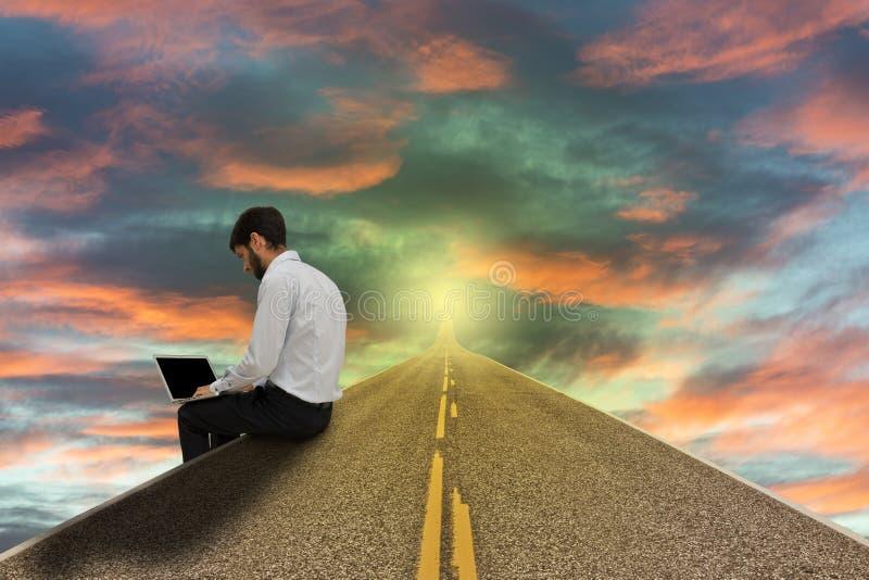 Zakenman die met laptop aan kant van de weg bij zonsondergang werken stock fotografie