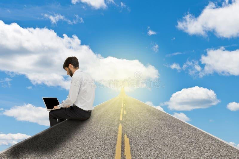 Zakenman die met laptop aan kant van de weg in de hemel werken royalty-vrije stock afbeelding