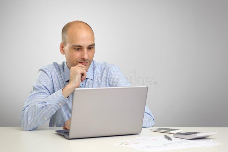 Zakenman die met laptop in bureau werken stock afbeeldingen