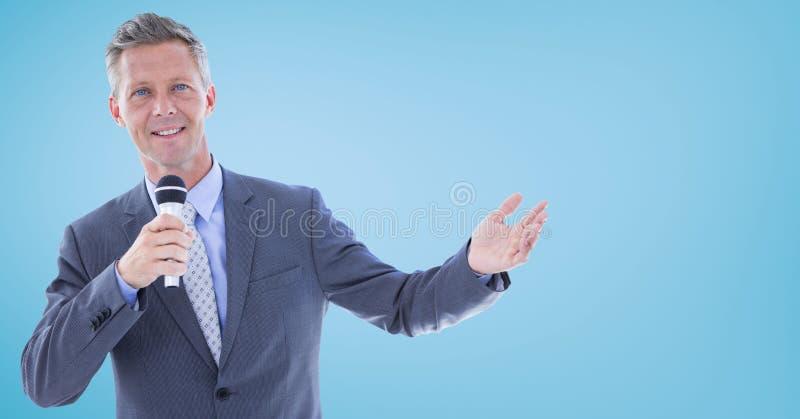 Zakenman die met microfoon tegen blauwe achtergrond spreken stock fotografie