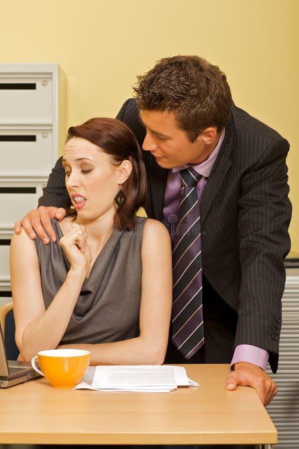 Zakenman die met onderneemster in bureau flirten stock foto's