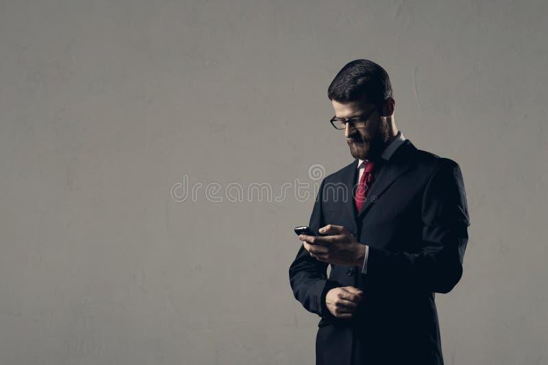Zakenman die met smartphone zich over witte muur bevinden stock fotografie