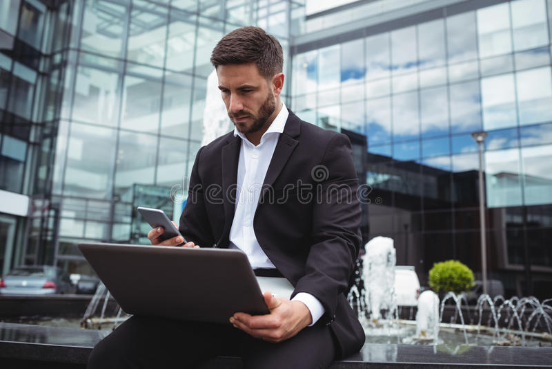 Zakenman die mobiele telefoon en laptop met behulp van stock afbeelding