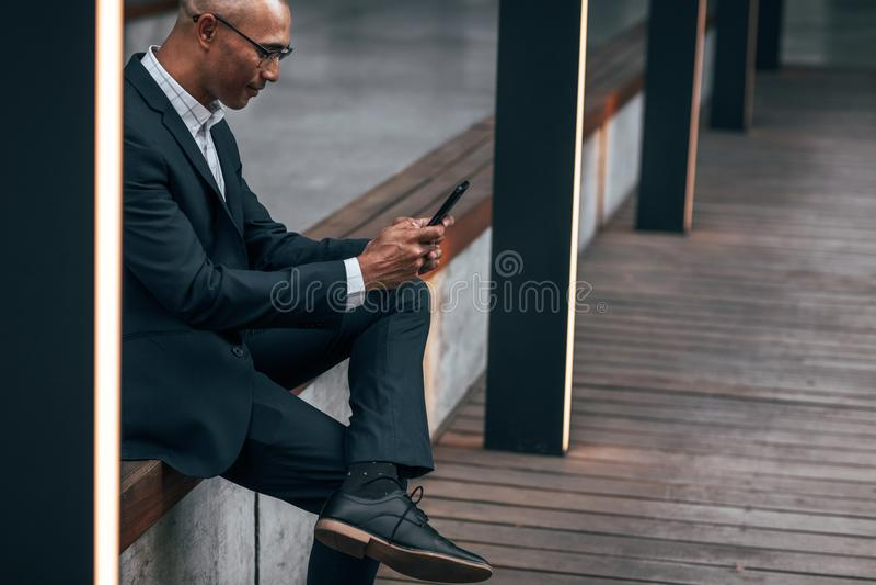 Zakenman die mobiele telefoonzitting in openlucht gebruiken stock afbeelding
