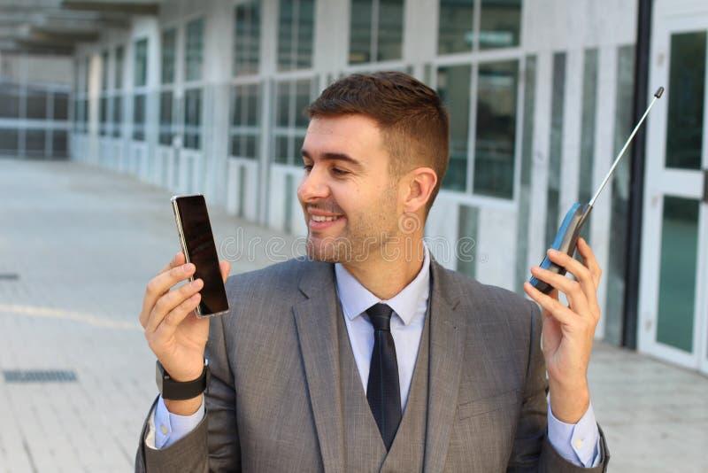 Zakenman die nieuwe en oude telefoon vergelijken royalty-vrije stock afbeelding