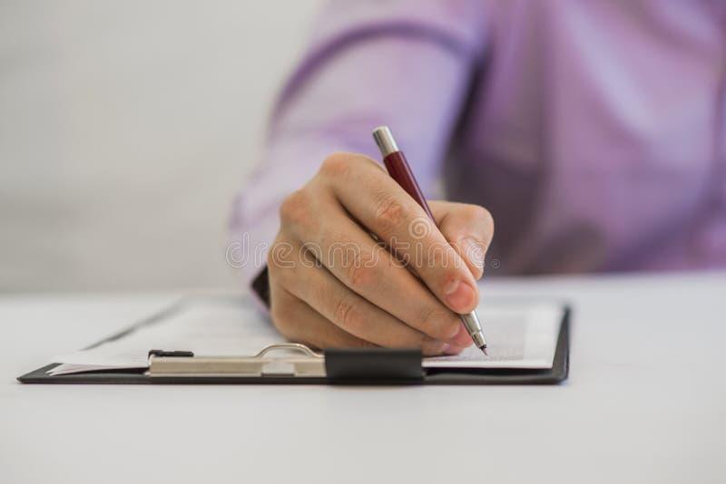 Zakenman die nota's over het document in zijn bureau maken royalty-vrije stock fotografie