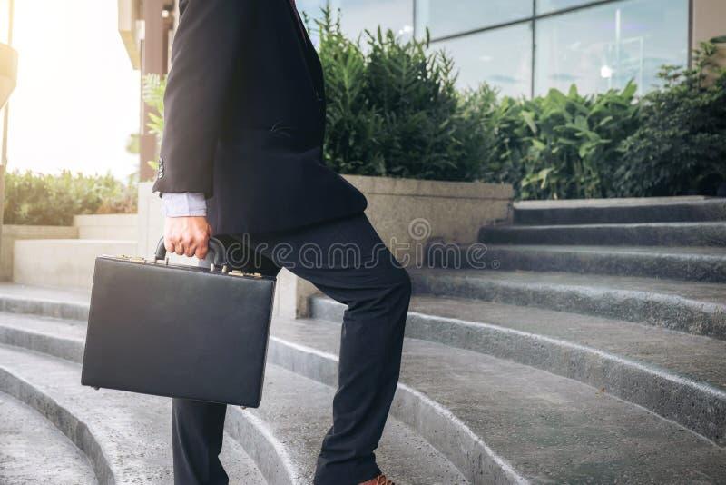 Zakenman die omhoog de treden lopen en een aktentas in han houden stock foto