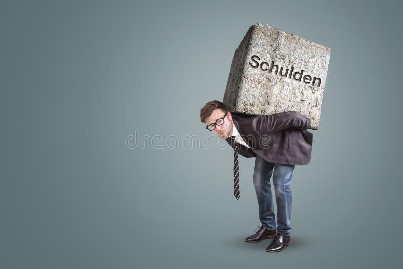 Zakenman die onder een zware steen met het Duitse die woord 'Schulden 'buigen op het wordt geschreven royalty-vrije stock foto's