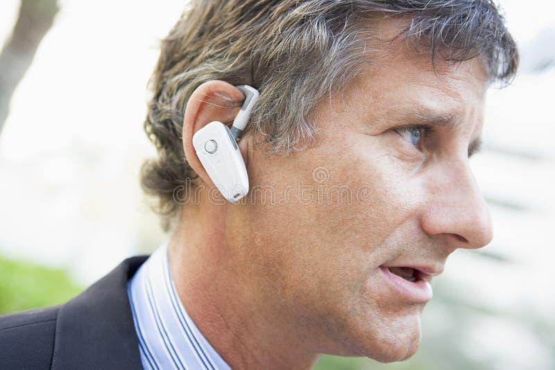 Zakenman die oortelefoon in openlucht draagt stock foto