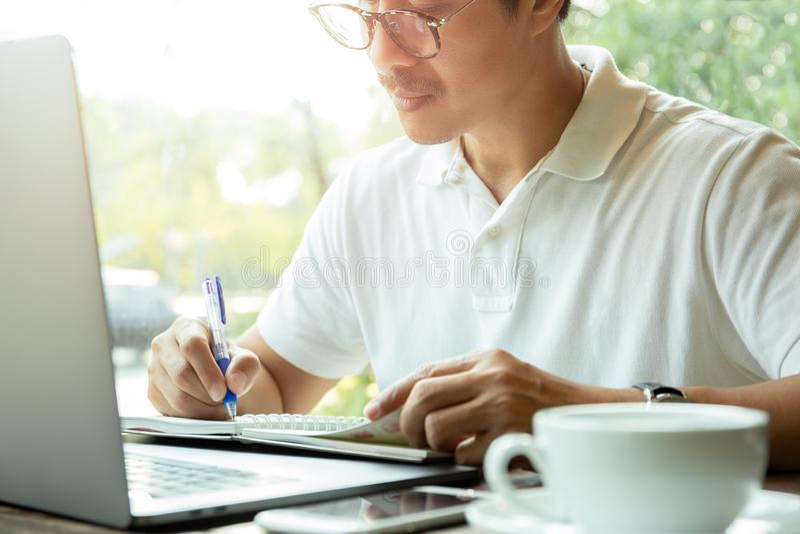 Zakenman die op blocnote voor laptop op houten bureau in koffiewinkel schrijven stock afbeelding