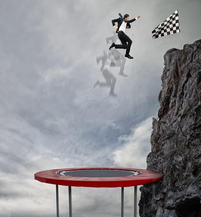 Zakenman die op een trampoline springen om de vlag te bereiken Voltooiings bedrijfsdoel en Moeilijk carrièreconcept royalty-vrije stock foto's
