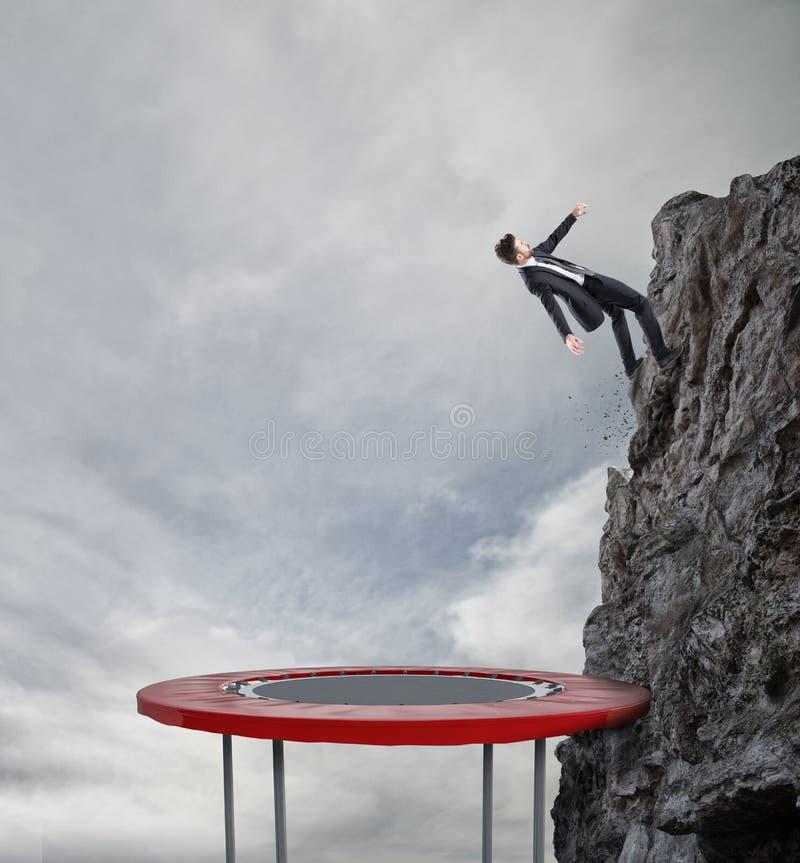 Zakenman die op een trampoline springen om de vlag te bereiken Voltooiings bedrijfsdoel en Moeilijk carrièreconcept royalty-vrije stock foto