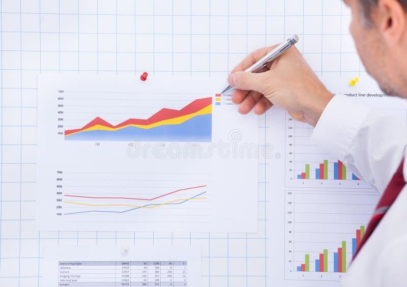 Zakenman die op grafiek schrijven stock afbeelding