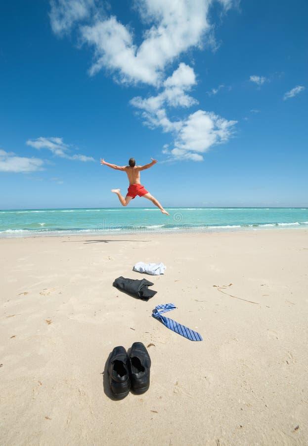 Zakenman die op het strand springt stock foto's